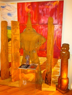 "In foreground: Four Taino mythology wood sculptures by Michael Auld (Jamaica, MD). In background: ""The Danzante de la Regla"" by Elio Beltran (Cuba, FL)."